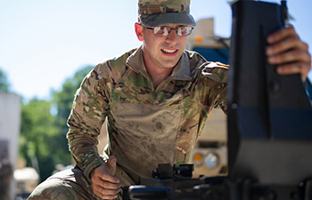 Man in military uniform working on a machine