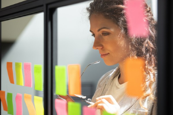 A woman ponders a series of sticky notes with career ideas on them.