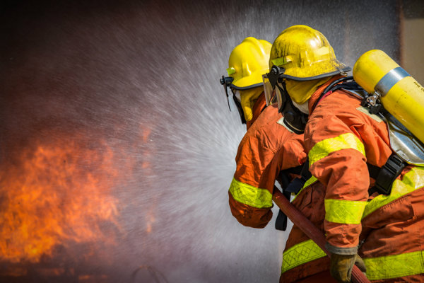 Firemen spray water on a fire