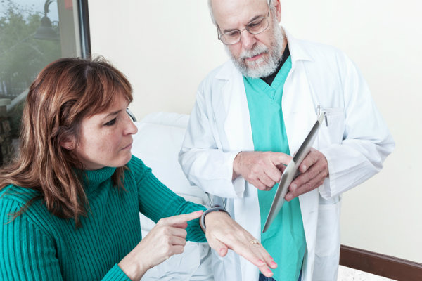 A doctor shows a patient how to use a health care app