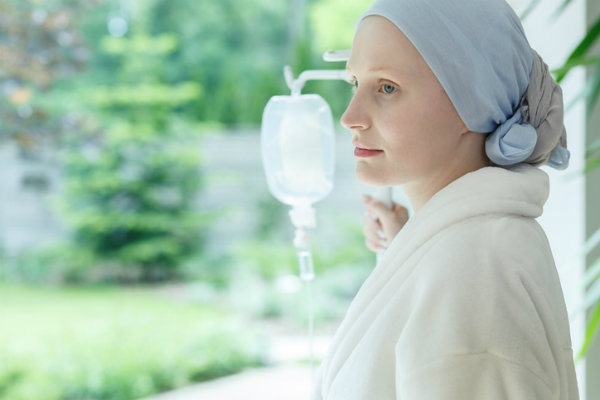 young woman cancer patient with head wrap by window