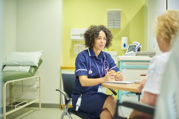 A nurse case manager speaks with a patient.