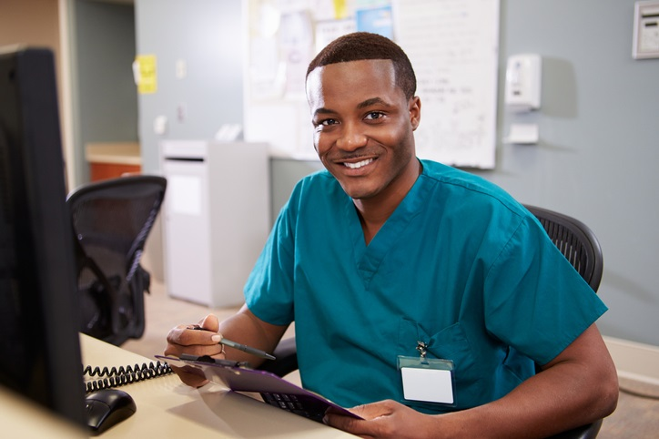 smiling male nurse in scrubs sitting at a front desk