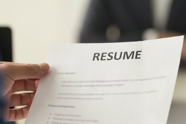A paper resume in a person's hand