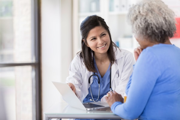 A health care professional talks to a patient