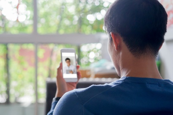 Young man using smartphone to video conference with telebehavioral health care provider