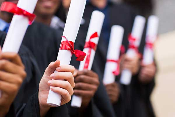 A group of graduates hold diplomas in their hands