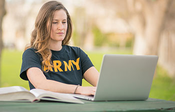 Women in Army T-shirt sitting outside working on a laptop