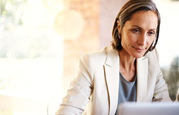 Middle aged woman in white blazer working on laptop