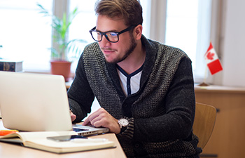 Canadian Man in glasses exploring financial options on laptop