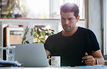 Man at home in black shirt shirt working on laptop
