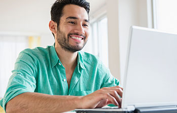 Man in green shirt working on laptop