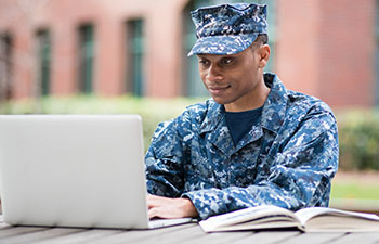 Man dressed in fatigues working on computer