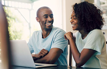 Man and women sitting in front of laptop looking at each other