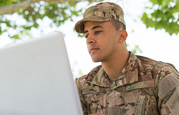 Man dressed in fatigues working on laptop