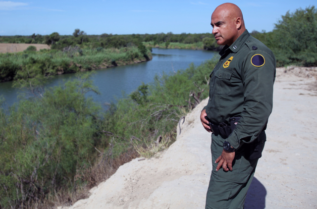 uniformed officer standing by a river
