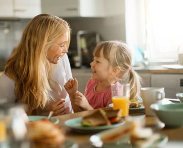 woman and young child eating breakfast