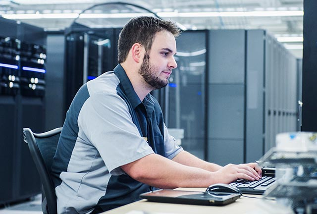 man at a computer in server room