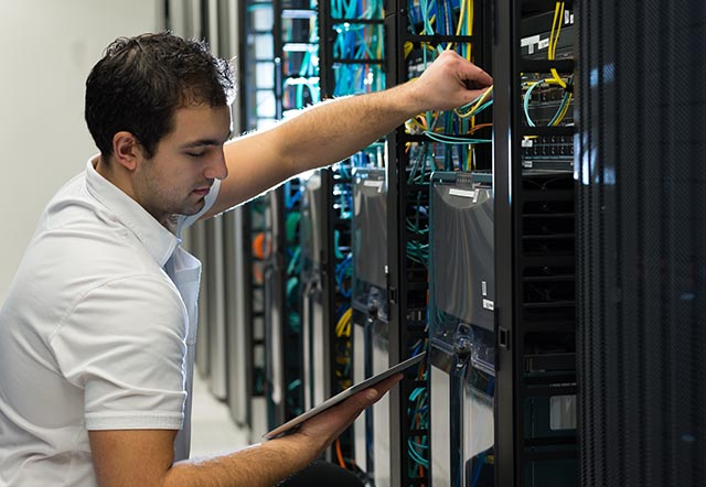 man working on computer in server room