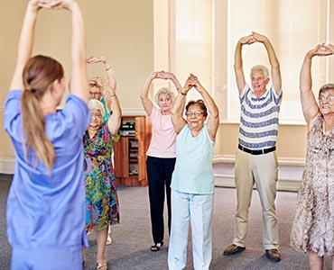 woman in scrubs leading exercise class for a group of elderly people