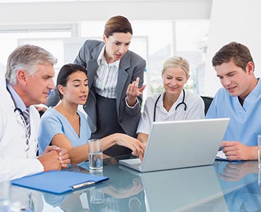 group of health care professionals looking at a laptop