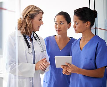 three health care professionals looking at tablet