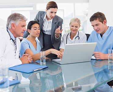 group of health care professionals looking at laptop