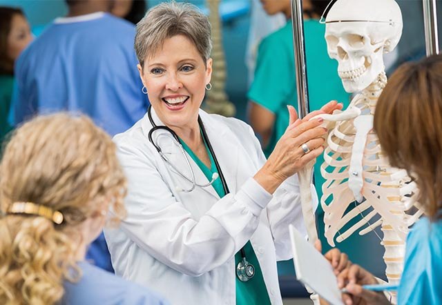 female nursing instructor pointing to human skeleton model