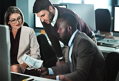 Female and two male coworkers in suits consulting together in front of a computer