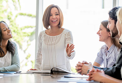 Woman addressing coworkers in a bright meeting room