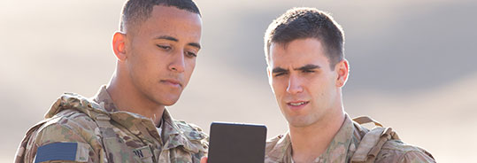 2 men in uniform looking at a tablet